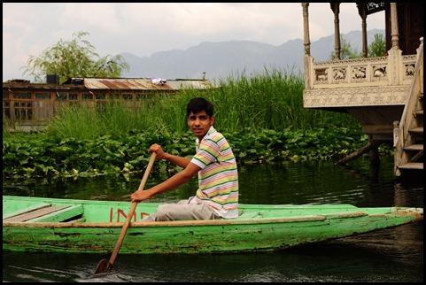 A boy steps out of a house-boat, Dal Lake, Srinagar