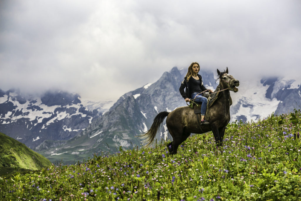 A Georgian girl enjoy riding in the vast meadows near Mkheri - Savaneti, Georgia