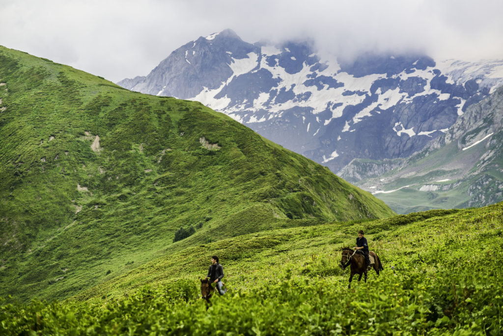 Locals riding with abandon amidst gorgeous scenery in the Caucasus mountains, Svaneti, Georgia